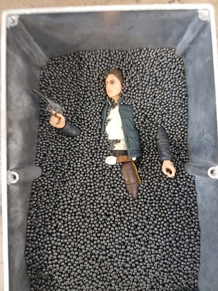 The aluminum box, partially filled with lead pellets and partially covering the Han Solo action figure