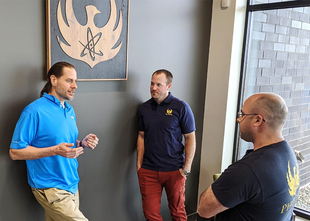 Greg Piefer, CEO of SHINE (left), talks with Evan Sengbusch, general manager of SHINE's Phoenix division, and Ross Radel, chief technology officer and chief operating officer of the Phoenix division, at the Phoenix Imaging Center in Fitchburg, Wis., on April 16, 2021.